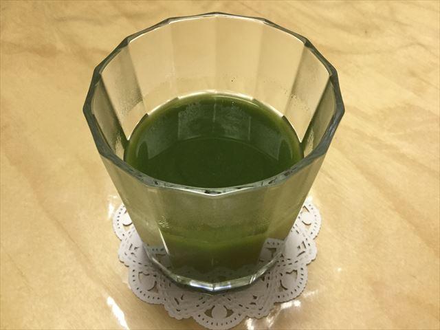 「三ツ星青汁レストラン極選青汁」の粉末をグラスに入れ、水で割った様子