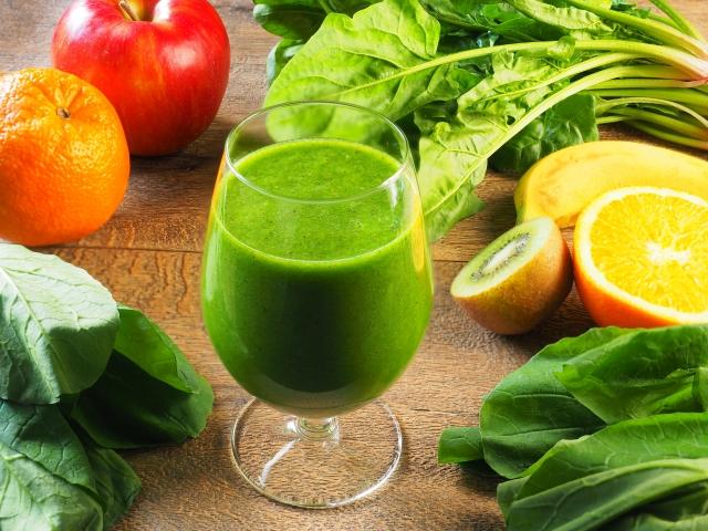 野菜ジュースが中央にあり、周りに野菜と果物が並んでいる